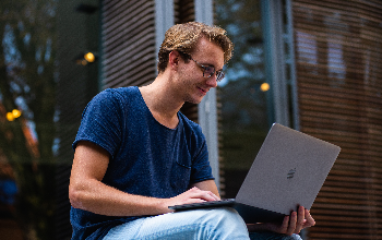 Male college student working on laptop outside of building